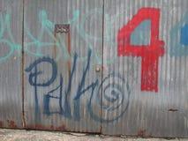 Graffiti op een geschilderde metaalmuur met 4 Royalty-vrije Stock Afbeelding