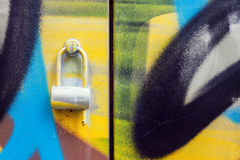 Graffiti painted doors with lock. Colorful background of spray painted doors with metal lock royalty free stock image