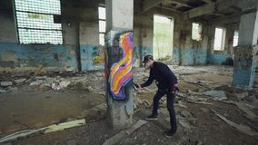 Graffiti painter is protective mask and gloves is drawing on old column in dirty empty building using aerosol paint. Young man is wearing casual clothes and stock video footage