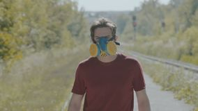Graffiti-painter in respirator sprays paint on camera. Slowly stock footage