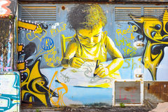 Graffiti painting of a kid studying. Stock Images