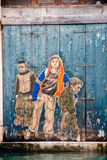 Graffiti portraying three boys on a wooden door of an old buildi Royalty Free Stock Photography
