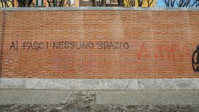 Graffiti on a red brick wall in Italian saying al fasci nessuno spazio, translated to no room for fascists - antifa theme. Milan, Italy - Feb 24, 2018: Graffiti Stock Images