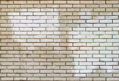 Graffiti removal with white paint over covering on brick wall. Masonry surface, removing acts of vandalism Royalty Free Stock Photo