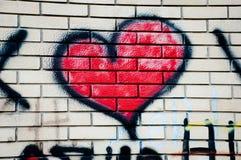 Graffiti rouge de coeur sur le mur de briques Image stock