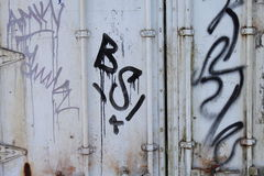 Graffiti on rusty container. Graffiti in black and violet on a white and rusty cargo container royalty free stock photos