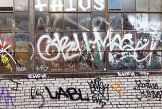 Graffiti-Schmutz umfasste Backsteinmauer-Hintergrund-Beschaffenheit Stockfotos