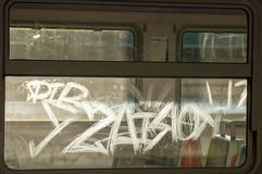 Graffiti scrawled on the glass of an electric train backlit by a backlight against an empty carriage royalty free stock images