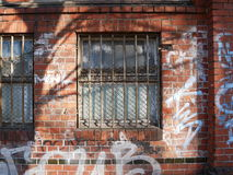 Graffiti scribbled on an exterior brick wall. Of a building with barred windows in an act of vandalism Royalty Free Stock Photos