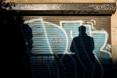 Graffiti and shadow of man. Graffiti and shadow of a man on wall Stock Photos