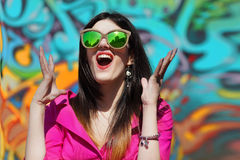 Graffiti Shouting. Girl with Sunglasses Shouting by a Painted Wall Royalty Free Stock Photography