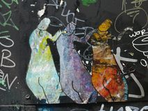 Graffiti depicting three figures standing next to each others. Graffiti showing three misterious figures standing next to each others against a black background Royalty Free Stock Photos
