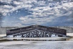 Graffiti in skatepark concrete wall on sky background. Abstract graffiti in skatepark concrete wall on sky background stock photography