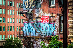 Graffiti and stairs on the side of a brick building seen from th Stock Photos