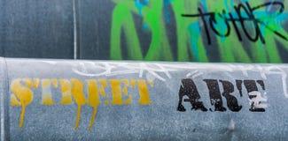 Graffiti on steam piping. Slogan street art on the steam pipe in a city. Creative graffiti stock photo