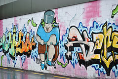 Graffiti street art. Illustrating a fat boy on a tricycle in colorful cartoonstyle Stock Photos
