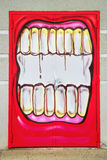 Graffiti - Street art. LAUDUN, FRANCE – May 08, 2014:  Graffiti  mouth painted on the door of the Forum sport center in Laudun, France on May 08, 2014 Royalty Free Stock Photography