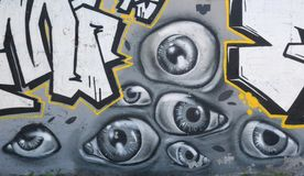 Graffiti art in the city street showing many painted eyes on the concrete gray wall as background.