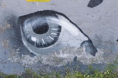 Graffiti art on the wall in the city street showing the painted eye on the gray concrete background.