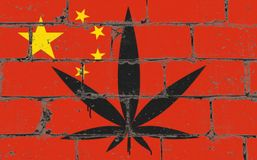 Graffiti street art spray drawing on stencil. Cannabis leaf on brick wall with flag China royalty free stock photos