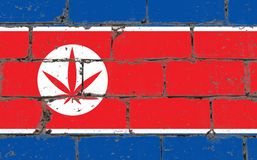 Graffiti street art spray drawing on stencil. Cannabis leaf on brick wall with flag North Korea stock photography