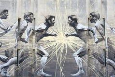Graffiti sulla gente fuggente della parete immagini stock