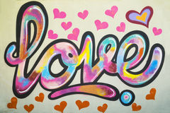 Graffiti text Love on the wall with many pink colored heart shapes around. Close up view Royalty Free Stock Photography