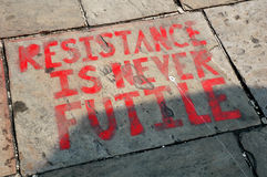 Graffiti text resistance is never futile. Pavement red bold Royalty Free Stock Image
