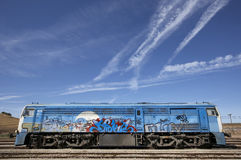 Graffiti on a train with railroad and blue sky. Royalty Free Stock Image