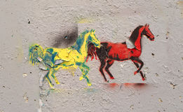 Graffiti of two horses peeling on concrete. A peeling graffiti image of two horses in bright paint on a concrete wall Royalty Free Stock Images