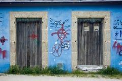 Graffiti und rustikale Türen auf einer blauen Wand Lizenzfreies Stockfoto