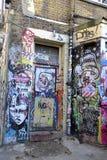 Graffiti in und um Ziegelstein-Weg London England lizenzfreie stockfotografie