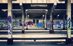 Graffiti under a bridge. Graffiti sprayed on cement walls under a bridge Royalty Free Stock Photography