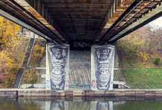 "Graffiti under a bridge in Vilnius. Creative graffiti under a bridge over Neris river in Vilnius, Lithuania. Two painted Atlant statues ""holding"" a bridge Stock Image"