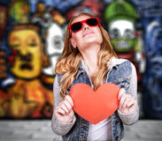 Graffiti urban lifestyle. Funky culture, stylish teen girl wearing sunglasses and holding red paper heart, modern love concept royalty free stock photography
