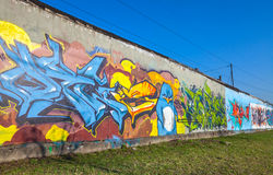 Graffiti variopinti sulle vecchie pareti concrete grige del garage Immagine Stock