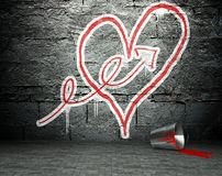 Graffiti wall with arrow and heart sign, street background Stock Image