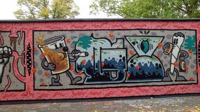 A graffiti wall in autumn. A colorful graffiti wall on a street with autumn leafs on the ground and trees behind it featuring beer drinking figures with funny royalty free stock photos
