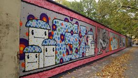 A graffiti wall in autumn. A fun smoking graffiti wall om a street with autumn leafs on the ground stock photography