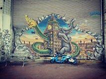 Graffiti on wall with custom bike. Big graffiti on shutters with custom bike in front stock photo