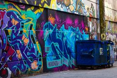 Graffiti on the wall by a dumpster stock photography
