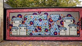 Graffiti wall with faces. A fun colorful graffiti wall om a street with autumn leafs on the ground and trees in the background stock photography