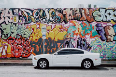 Graffiti wall. Graffiti in Miami's Wynwood district, contrasting with clean white car Royalty Free Stock Photos