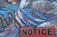 Graffiti on wall with Notice sign in Portland, Oregon. This is graffiti on a wall with a painted Notice sign in Portland, OR Royalty Free Stock Images