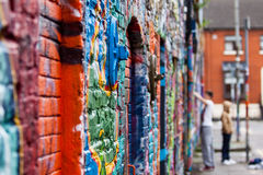 Graffiti wall with painters. Graffiti on the wal with teenagers in the backsground Stock Photography