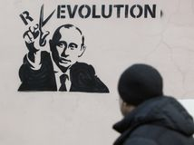 Putin and Revolution. Graffiti on the wall. President Putin cuts the letter off the word Revolution with scissors Stock Photos