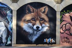 Graffiti on a wall showing the face of a fox. Graffiti on a run down building showing the face of a fox  staring into space Stock Photo
