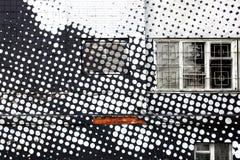Graffiti on the wall - white circles. White circles on a black brick wall graffiti Stock Photography