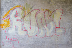 Graffiti on a wall with the word Run. Scribbled painted graffiti on an old cement wall with the word Run possibly written in protest by an activist or in anarchy Stock Photos