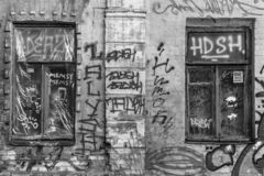 Vandalized facade of an old building. Graffiti on the walls of the old house. Street art. The painted facade of an abandoned house. Urban style. Dysfunctional royalty free stock image